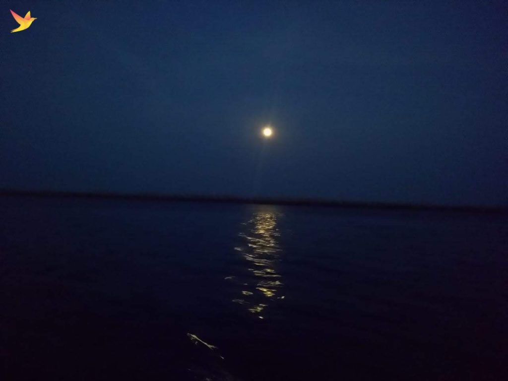 Full moon from blue sky reflecting on the blue sea